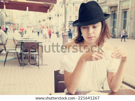Young pretty woman in street cafe with cup  - stock photo