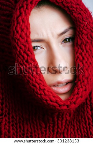 young pretty woman in sweater and scarf all over her face, winter cold - stock photo