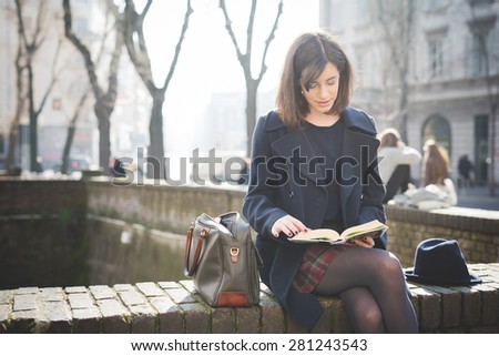 young pretty woman in town reading book - stock photo