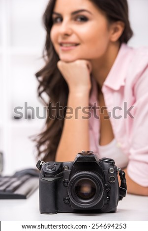 Young pretty woman is looking at you. Focus on camera. - stock photo