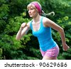 Young pretty woman jogging in the green park - stock photo