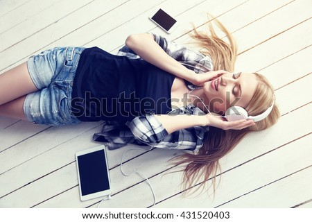 young pretty woman listening music in headphones lying on a wooden white floor at home - stock photo