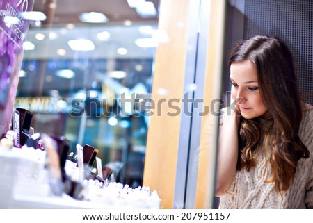 Young pretty woman looks at display through the glass in jewelry store - stock photo