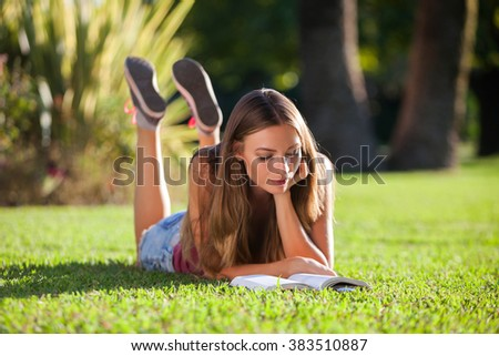 Young pretty woman lying and reading book on a grass - stock photo
