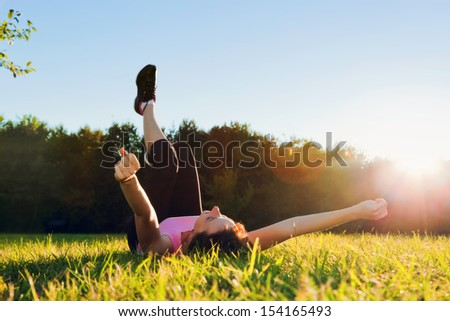 Young pretty woman lying and streching herself on the grass at summer sunset. Relaxation, balance and harmony. - stock photo