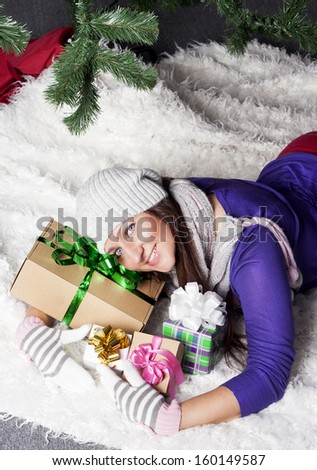 Young pretty woman near xmas tree with presents - stock photo