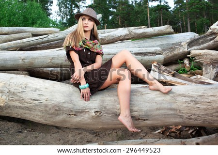 Young pretty woman on logs in the forest - stock photo