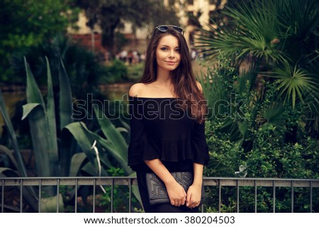 Young pretty woman outdoor summer portrait. Attractive girl posing against green tropical plants