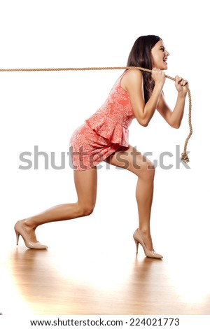 young pretty woman pulling a rope - stock photo