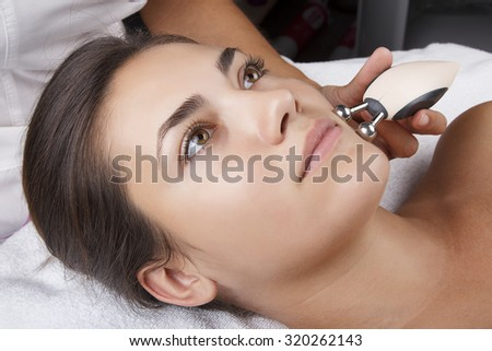 Young pretty woman receiving treatments in beauty salons. Young beautiful dark-haired woman in the office beautician lying on the couch. Miostimulation procedure. Hardware cosmetology. - stock photo