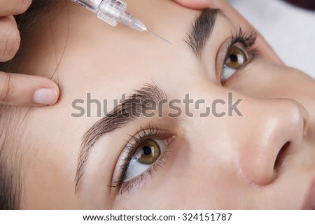 Young pretty woman receiving treatments in beauty salons. Young beautiful dark-haired woman in the office beautician lying on the couch. ?ontouring procedure , revitalization. Beauty injections . - stock photo