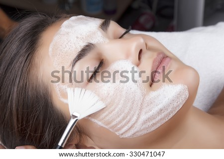 Young pretty woman receiving treatments in beauty salons. Young beautiful dark-haired woman in the office beautician lying on the couch. Facial cleansing foam using. - stock photo