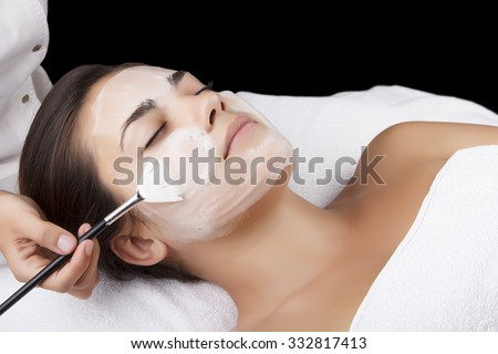 Young pretty woman receiving treatments in beauty salons. Young beautiful dark-haired woman in the office beautician lying on the couch. Facial cleansing foam using. Isolated black. - stock photo