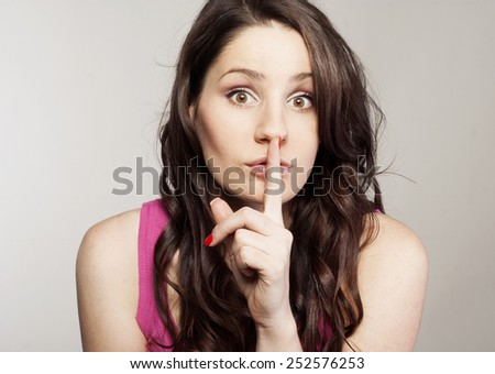 Young pretty woman saying shh - stock photo