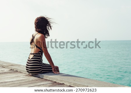 Young pretty woman sitting alone on the pier near the sea and looking on the water and waiting for somebody in ocean - stock photo