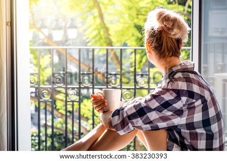 Young pretty woman  sitting at opened window drinking coffee and looking outside enjoys of rest. Dream - stock photo