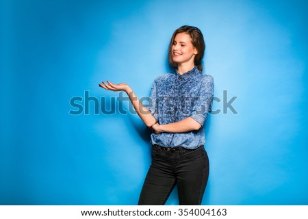 young pretty woman smilig in blue shirt standing on blue background, showing one side - stock photo