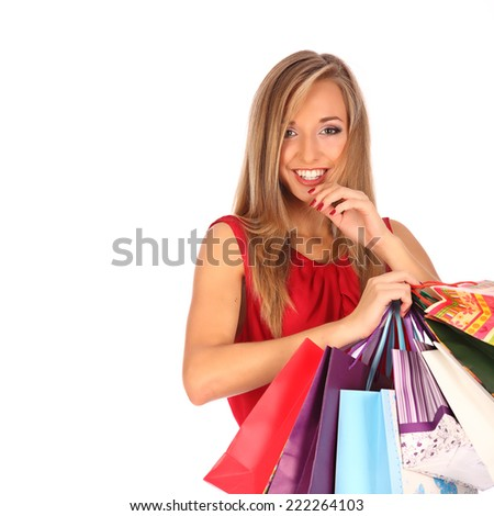 young pretty woman standing with colourful shopping bags, studio - stock photo