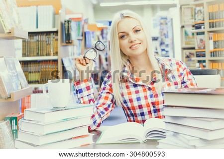 Young pretty woman studying in library - stock photo