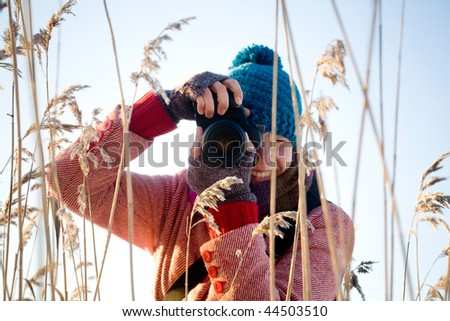 Young pretty woman taking nature pictures outdoors - stock photo