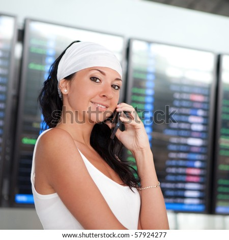 Young pretty woman talking on mobile phone in the airport - stock photo