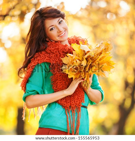 Young pretty woman walking in the autumn park - stock photo
