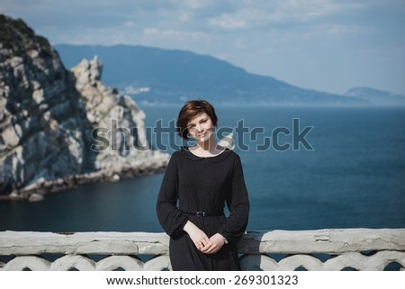 Young pretty woman with a short haircut standing on a balcony in a fashion dress with beautiful view on the background - stock photo