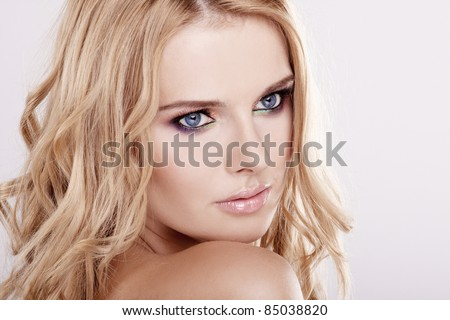 Young pretty woman with beautiful blond hair and multicolor makeup isolated on white background - stock photo
