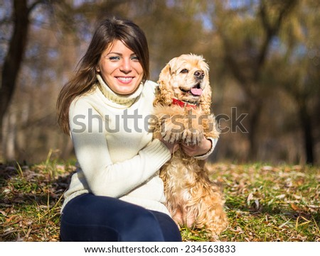Young pretty woman with her dog American Cocker Spaniel sitting in city park in sun lights in autumn  - stock photo