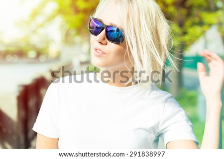Young pretty woman with platinum blond hair in trendy sunglasses with reflections in the summer - stock photo