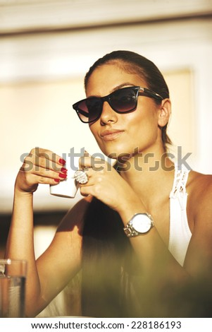 Young pretty woman with pony tail, sunglasses and wrist watch, drinking coffee in a cafe, outdoors - stock photo