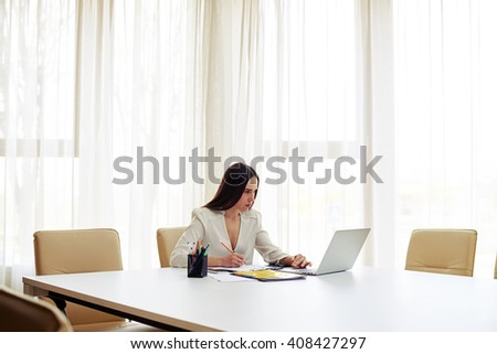 Young pretty woman working on her laptop and writing some data in a pad  in white modern office - stock photo