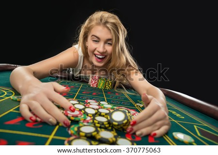 Young pretty women playing roulette wins at the casino - stock photo