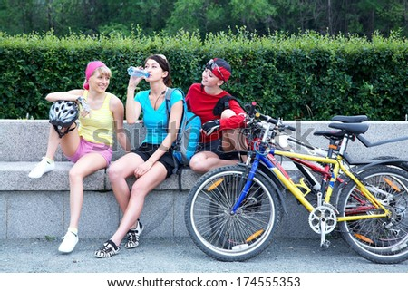 Young pretty women resting after cycle race in the green park  - stock photo