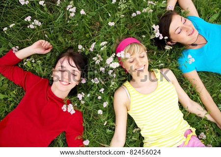 Young pretty women resting on the green grass in summer - stock photo