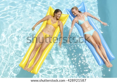 Young pretty women with perfect tanned body lying on yellow and blue air mattresses in the pool in summer and having fun - stock photo