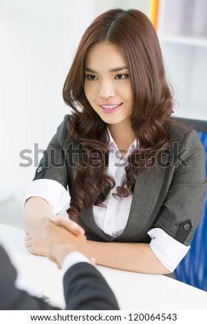 Young pretty worker shaking hands with her employer - stock photo