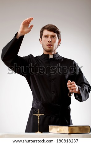 Young priest is preaching a sermon and holding a rosary - stock photo