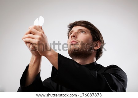 Young priest wearing black cassock is celebrating a Holy Mass with wafer - stock photo