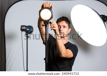 Young pro photographer in his studio setting up lights for the upcoming photoshoot (color toned image; shallow DOF) - stock photo