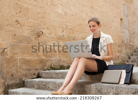 Young professional business woman sitting on the steps of an old stone building using a laptop computer working outdoors, smiling. Connectivity and wireless internet browsing. - stock photo