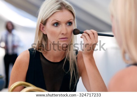 young professional businesswoman applying makeup cosmetics early morning at home bathroom - stock photo