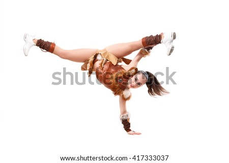 Young professional cheerleader dressed in a warrior costume standing on one hand. Horizontal splits - stock photo