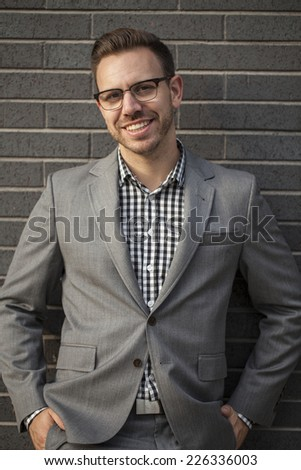 Young professional in business attire projecting confidence against brick wall - stock photo