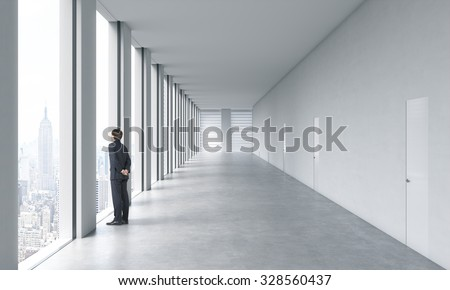 Young professional in formal suit is looking out the window. Empty modern bright clean interior of an open space office. Huge panoramic windows with New York view. - stock photo