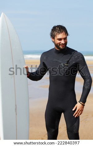 Young professional surfer smiling standing on beautiful ocean beach with his white surfboard, attractive brunette man dressed in wetsuit ready to surfing on big ocean waves at sunny autumn day - stock photo