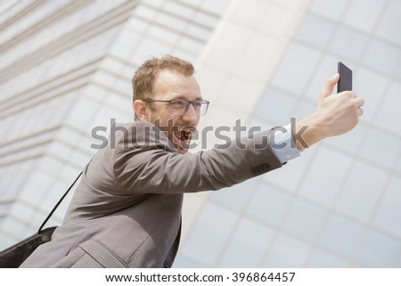Young professional taking selfie in front of the blue glass business building   - stock photo
