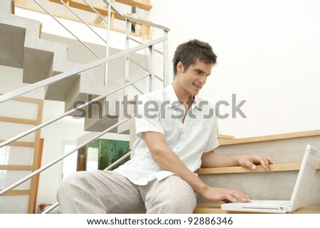 Young professional using a laptop while sitting in a modern stairwell. - stock photo