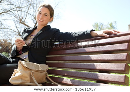 Young professional woman sitting on a wooden bench in a city park, holding her smartphone and smiling at the camera during a sunny day. - stock photo