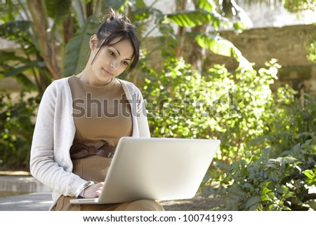 Young professional woman using a laptop computer in the park on a sunny day. - stock photo